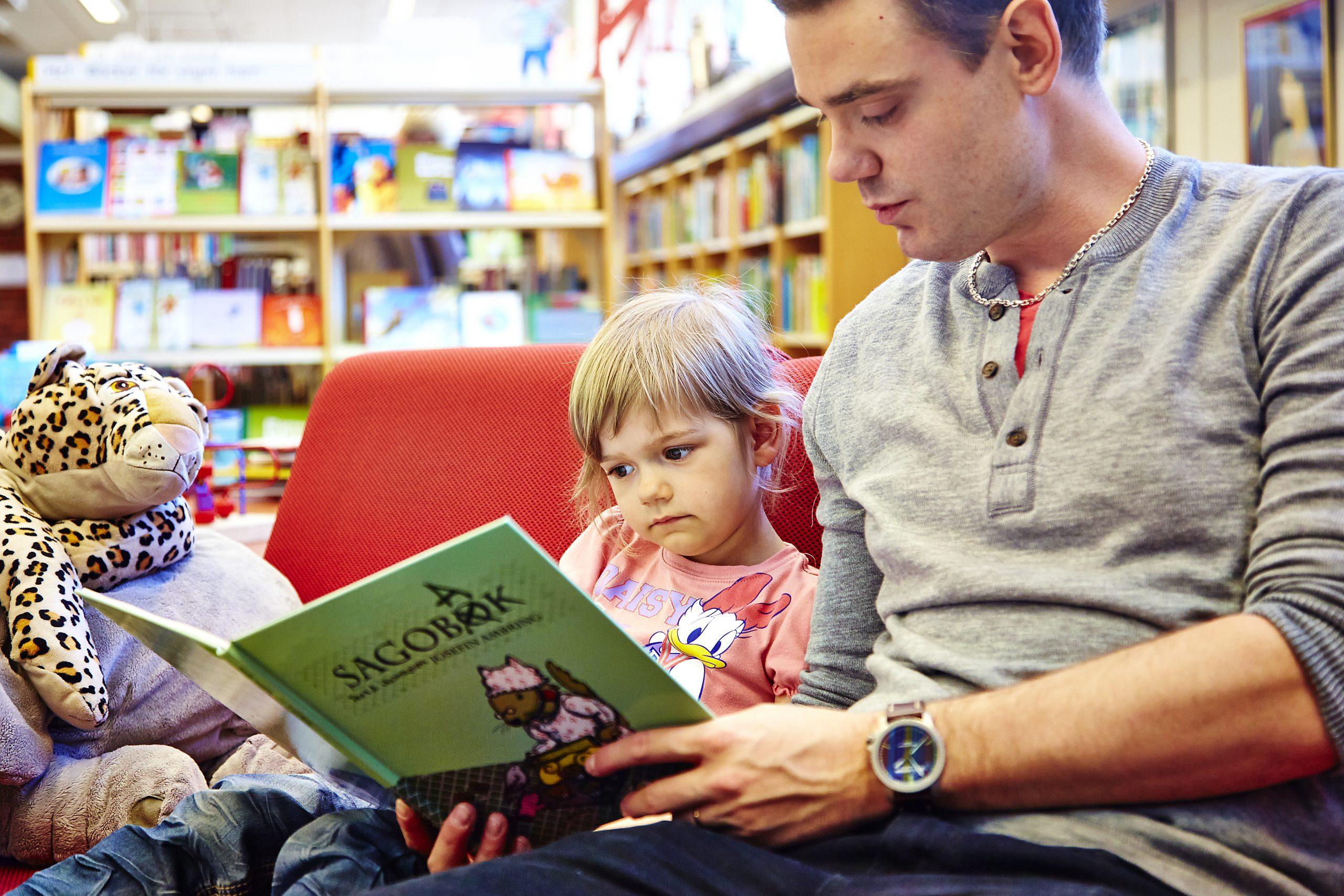 En vuxen läser en sagobok för ett barn på Västerås Stadsbibliotek. Fotograf: Hans Nordlander