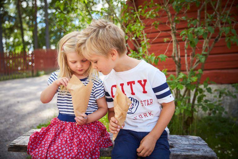 Barn sitter på en sten på Vallby Friluftsmuseum och äter godis från den gamla handelsboden. Fotograf: BildN