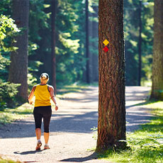 Kvinna promenerar i spåret på Björnö. Fotograf: Pia Nordlander