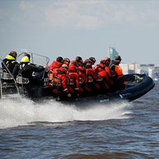 En RIB-båt med en grupp människor åker fram på mälaren med Skrapan i bakgrunden. Foto: Pressbild