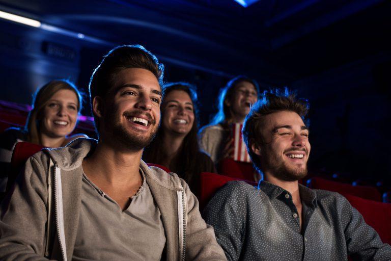 Ett par glada män ser på bio. Fotograf: Mostphotos