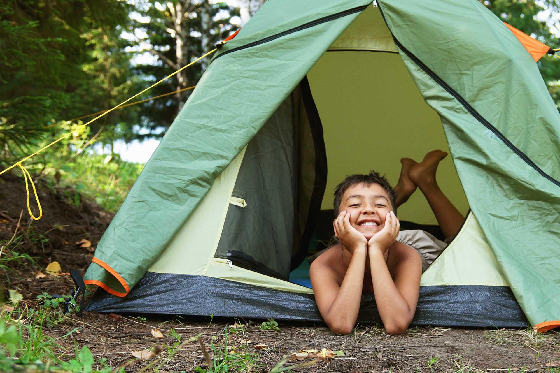 Ett glatt barn i tält på camping. Foto: Mostphotos