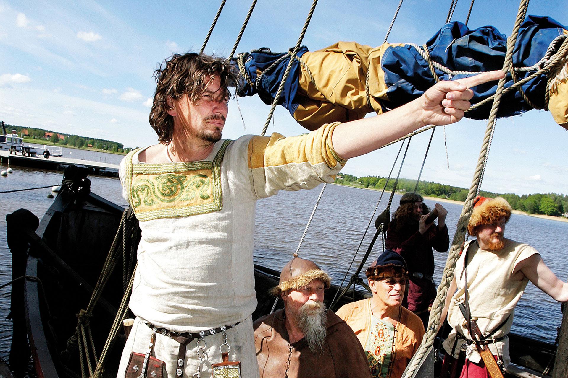 Män i vikingakläder åker i roddbåt vid gästhamnen på Frösåkers Brygga. Fotograf: Kenneth Hudd