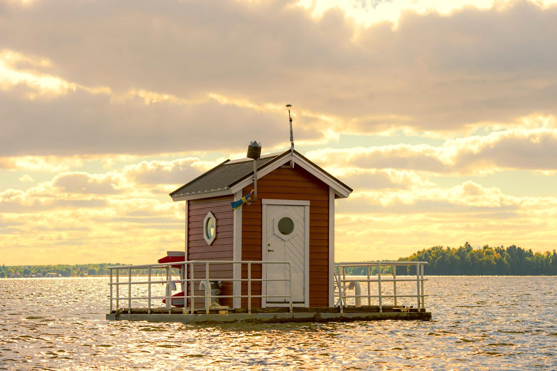 Undervattenshotellet Hotell Utter Inn, en röd liten flytande stuga, på Mälaren i solnedgång en sommarkväll. Fotograf: Leon Grimaldi