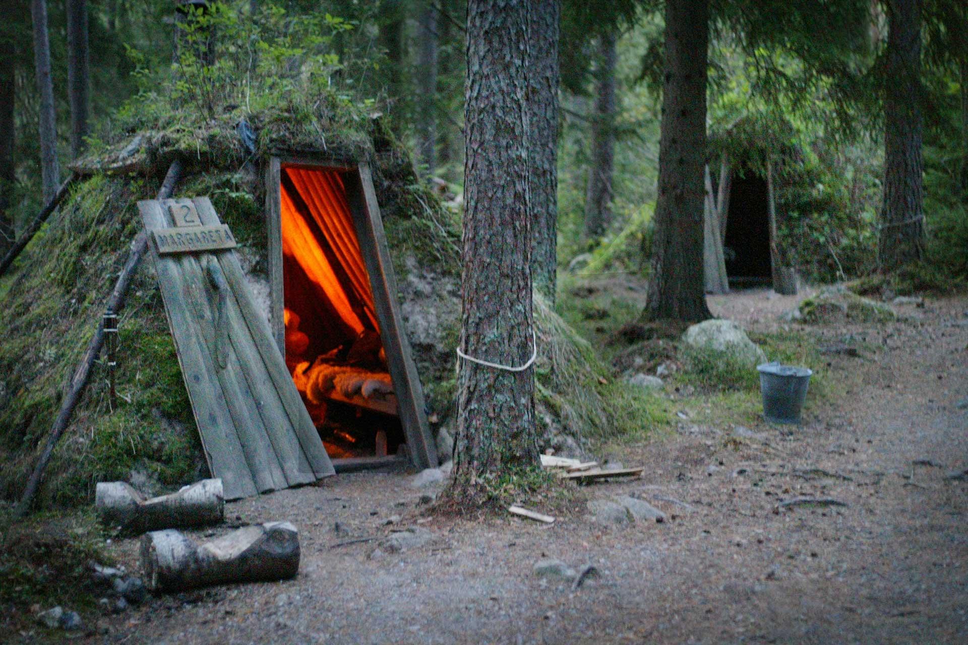 I den gröna skogen lyser det från eldstaden inne i kolarstugan på Kolarbyn. Fotograf: Mikaela Larm