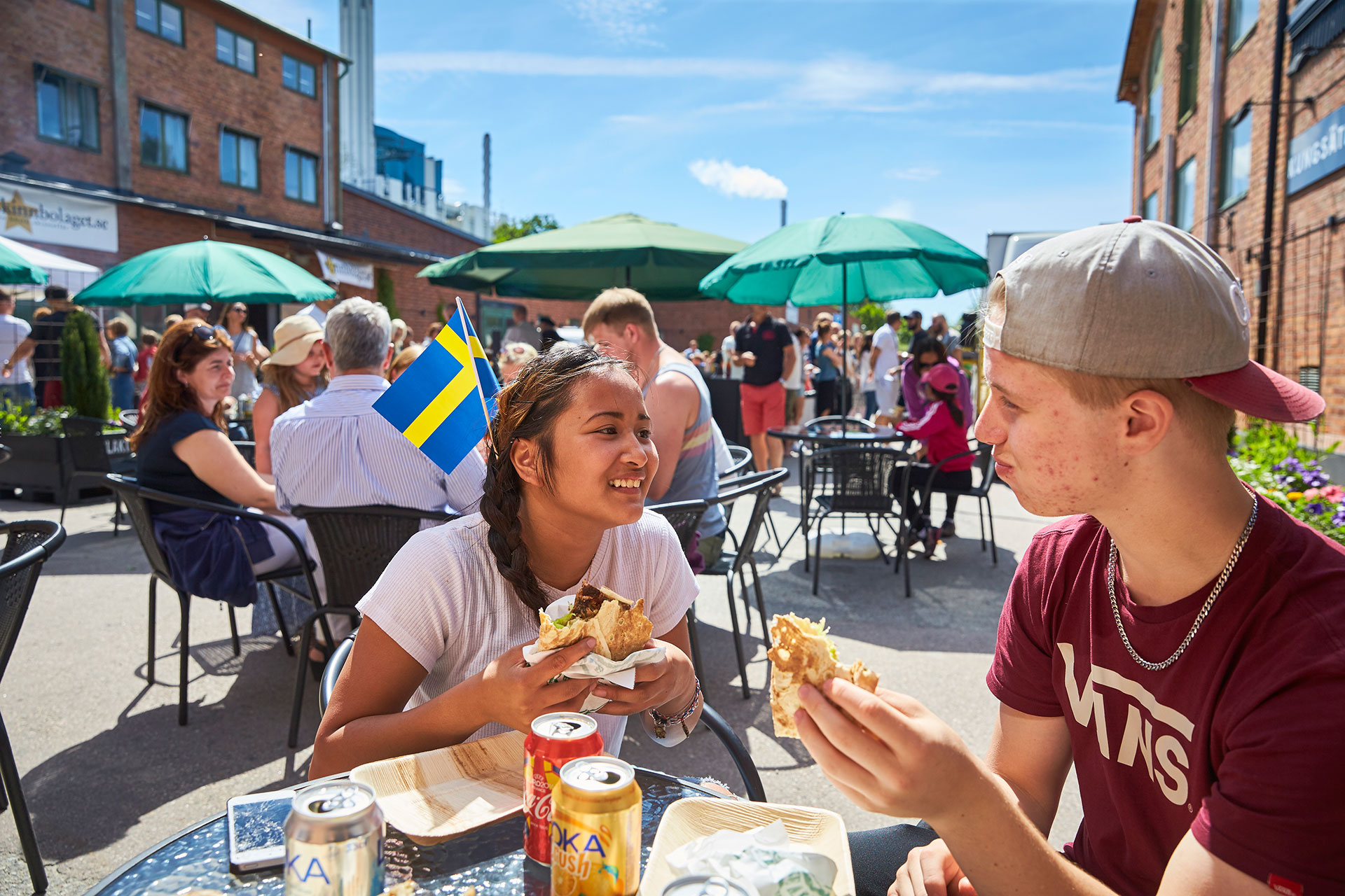 Två tonåringar äter mat från Saluhallen Slakteriet utomhus i solen. Fotograf: BildeN
