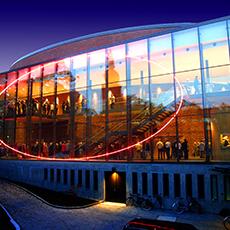 Bild visar fasad ett stort glashus med en stor rund ring i neon. Fotograf: Clifford Shirley