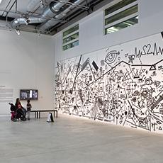 Bild beskriver en vägg med konst, en kvinna sitter längst ned i vänster hörn: Fotograf: Bo Gyllander