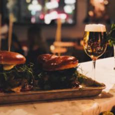 Bild beskriver en bricka med 2 hambugare och ett vinglas med öl.