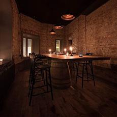 Bilden visar ett bord och stolar med fönster åt ena hållet och tegelvägg åt andra inne på Vinoteket Lothar.