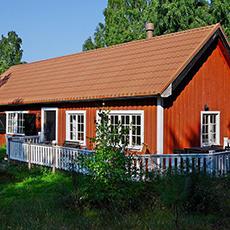 Bilden visar en av stugorna som man via Sjöevent kan hyra på Aggarön. Stugan är röd med vita knutar.