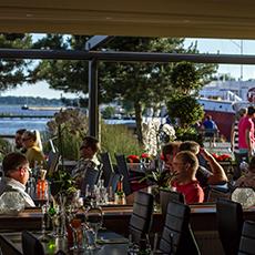 Middagsgäster som sitter på uteserveringen på Agrill, med utsikt över Mälaren. Foto: Pressbild