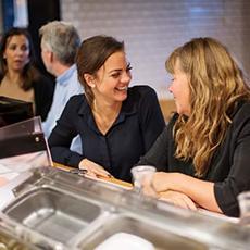 Två glada kvinnor som sitter och väntar på sin mat på Aurora Sushi Bar i Saluhallen Slakteriet. Foto: Pressbild