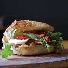Bilden visar en pizzapanino fylld med salami, buffelmozzarella, sallad och tomat som man kan beställa inne på Bisnonno Bar.