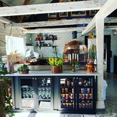 Välkomstdesken och vedugnen som pizzorna bakas i på Bistro Lilla Stallet. Foto: Pressbild