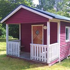 Bilden visar en liten stuga som man kan hyra hos Björnögårdens stugor.