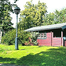 Bilden visar en röd stuga som ligger intill Café Björnen.