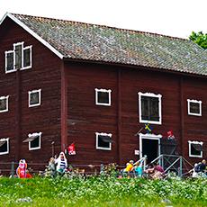 Bilden visar det röda trähuset som Café Magasinet ligger i på Ridön. Fotograf Mostphotos.