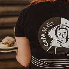 Bilden visar ryggen på en i personalen som har en t-shirt med trycket Café Malin. Fotograf: Henrik Mill.