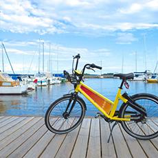 Bilden visar en gul DigiBike som står på en brygga med Mälaren och båtar i bakgrunden.