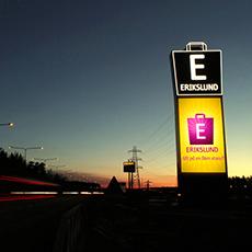 Bilden visar en stor vägskylt med hänvisning till Erikslunds handelsområde från E18.