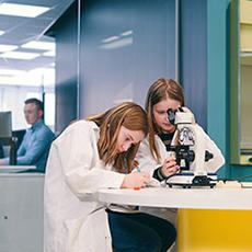 Bilden visar två tjejer som sitter med ett mikroskåp på expectrum. Fotograf: Af Adam.