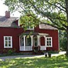 Bilden visar en röd träbyggnad med vita knutar på Finnsta Gård.