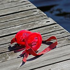 Ett par röda simglasögon som ligger på en brygga på Framnäsbadet. Foto: Pressbild