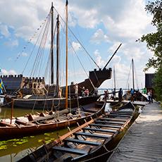Bilden visar flera vikingabåtar samt koggen Roter Teufel på Frösåkers Brygga.