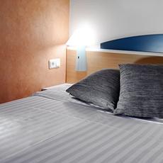 Bilden visar en nybäddad säng med kuddar inne på Good Morning Hotel.