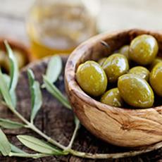 En träskål med gröna oliver och en olivkvist som symboliserar restaurangen Grekiska Grill och Bar. Foto: Pressbild
