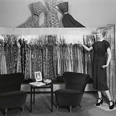 En skyltdocka och en rad upphängda klänningar Från H&Ms första butik i Världen, i Västerås. Foto: Pressbild från H&Ms bildarkiv.
