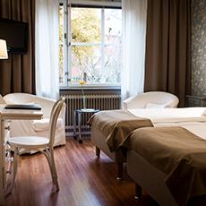 Bilden visar ett av rummen på hotell Arkad med sängar, fåtöljer och ett skrivbord.