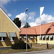 Bilden visar de gula byggnaderna som innefattar Hotell Hässlö.