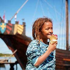 Pojke i blå tröja äter glass men ett vikingaskepp i bakgrunden. Fotograf: Pia Nordlander
