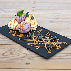 Bilden visar glasskulor med grädde, kolasås och blåbär på Glassverket Kokpunkten.