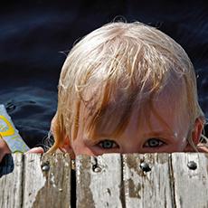 Ett barn som tittar upp i från bryggkanten på Lövuddens Badplats. Foto: Västmanlands kommuner och landsting