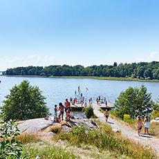 En badvik på ön Östra Holmen med många personer som står på en brygga. Fotograf: Pia Nordlander