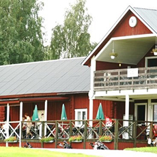 Bilden visar en stor röd fasad med uteservering