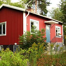 En stor röd stuga med en blå dörr