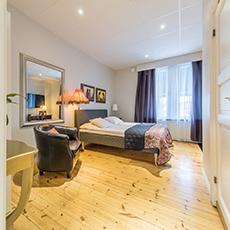 En hotellsäng med en fotölj