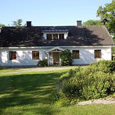 Bilden visar ett stort vitt hus.