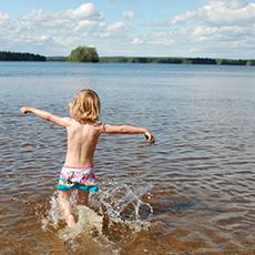 En pojke som springer ut i vattnet på Sundängens Badplats. Foto: Pressbild