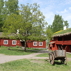 Bilden visar små röda hus med en gammal vagn. Fotograf Nina larsen Welander