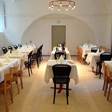 Bild beskriver en sal med flera bord med vita dukar och fin dukning