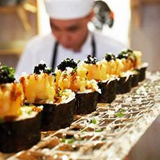 Bild visar mat på rad med kocken i bakgrunden.