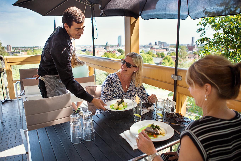 Några matgäster serveras på Djäknebergets restaurang med vy över Västerås stad. Fotograf: Findie