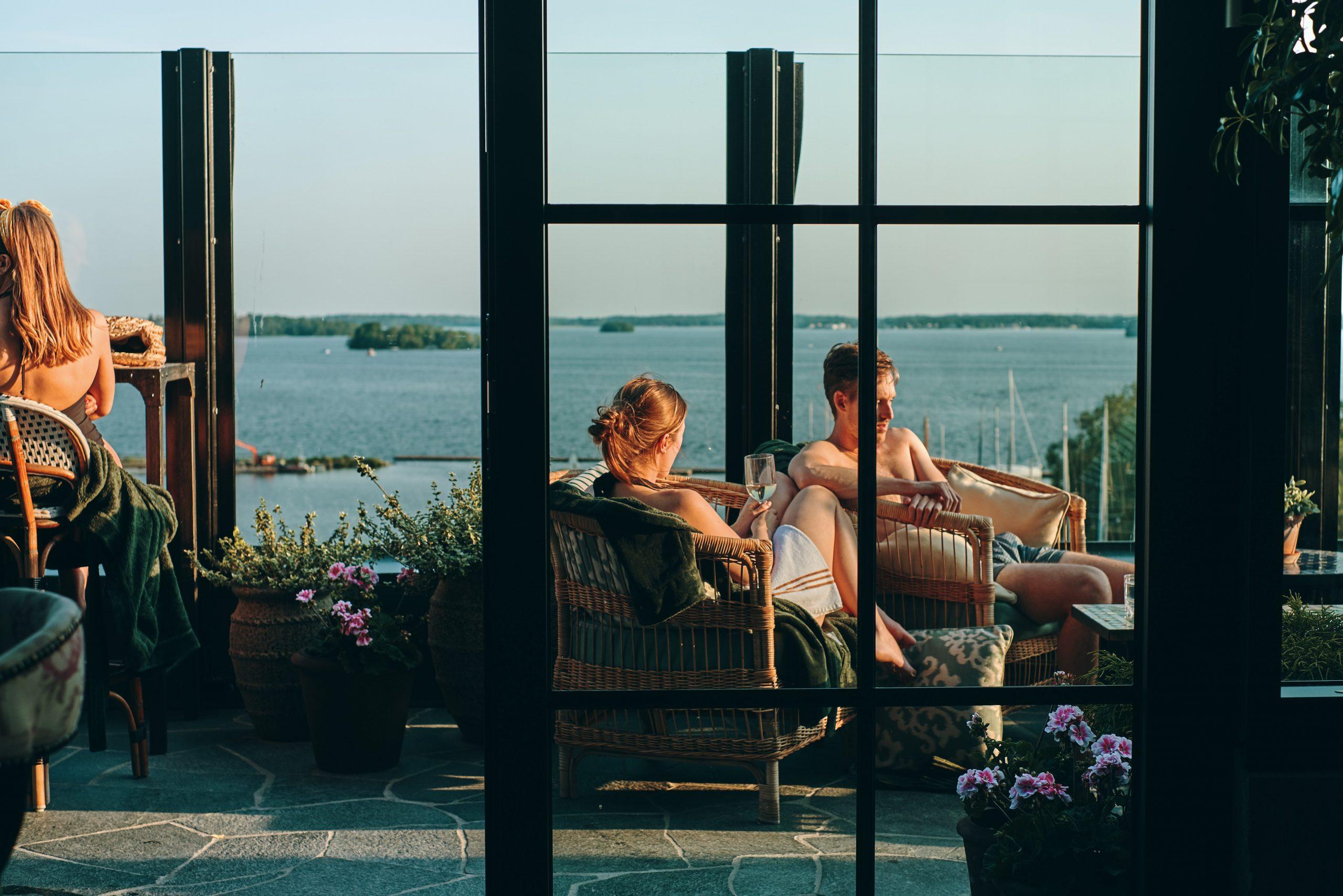 Några personer sitter i solen på utomhusterassen på Steam Hotel och deras Spa. Med vy över mälaren. Fotograf: Adam Af Ekenstam