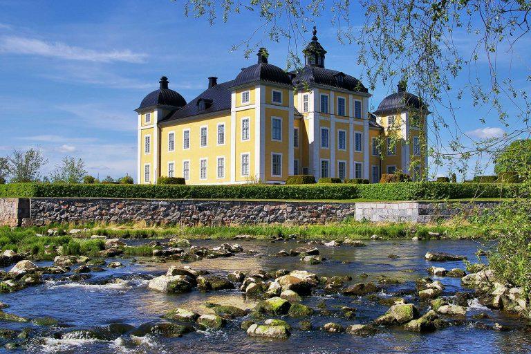 Strömsholms slott tornar upp sig i solljuset. Ett vattendrag i förgrunden. Fotograf: Pressbild