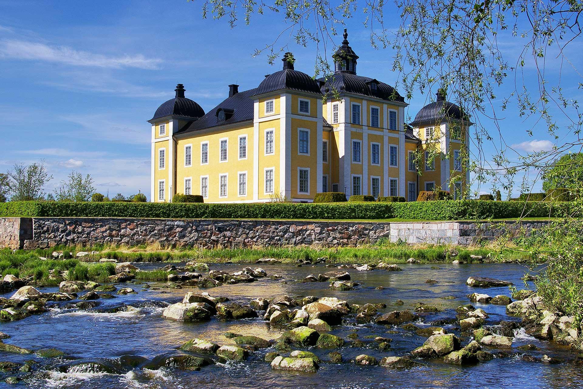 Strömsholms slott tornar upp sig i solljuset. Ett vattendrag i förgrunden. Foto: Mostphotos